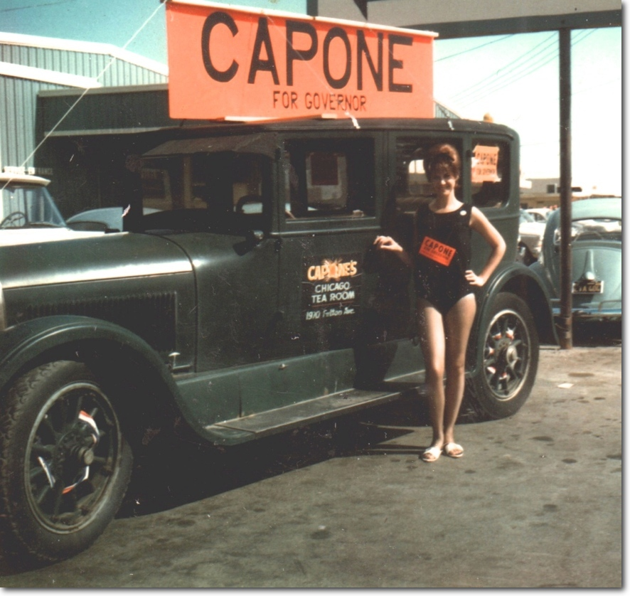 Photo of an old auto with a Capone campain sign above the roof