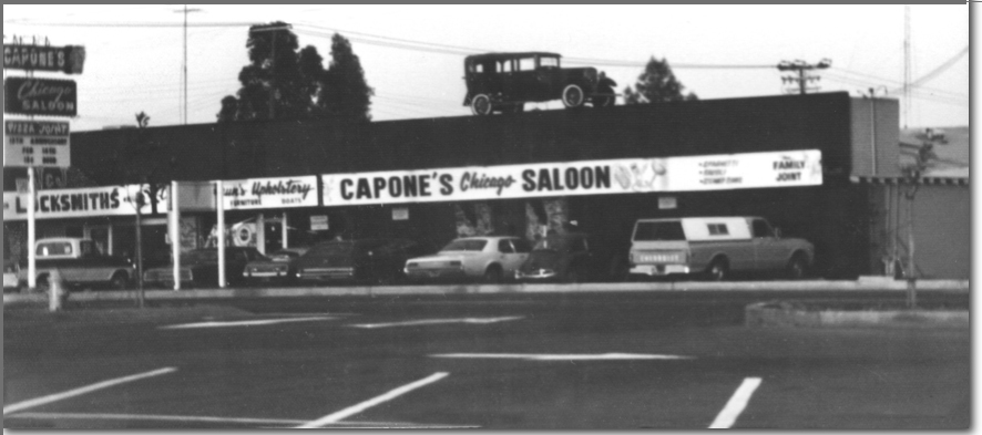 Photo of Capone's. Big sign across the front reading, Capone's Chicago Saloon. To enter the front door, you had to enter a phone booth and turn the crank on the old phone. An old car sits on the roof.