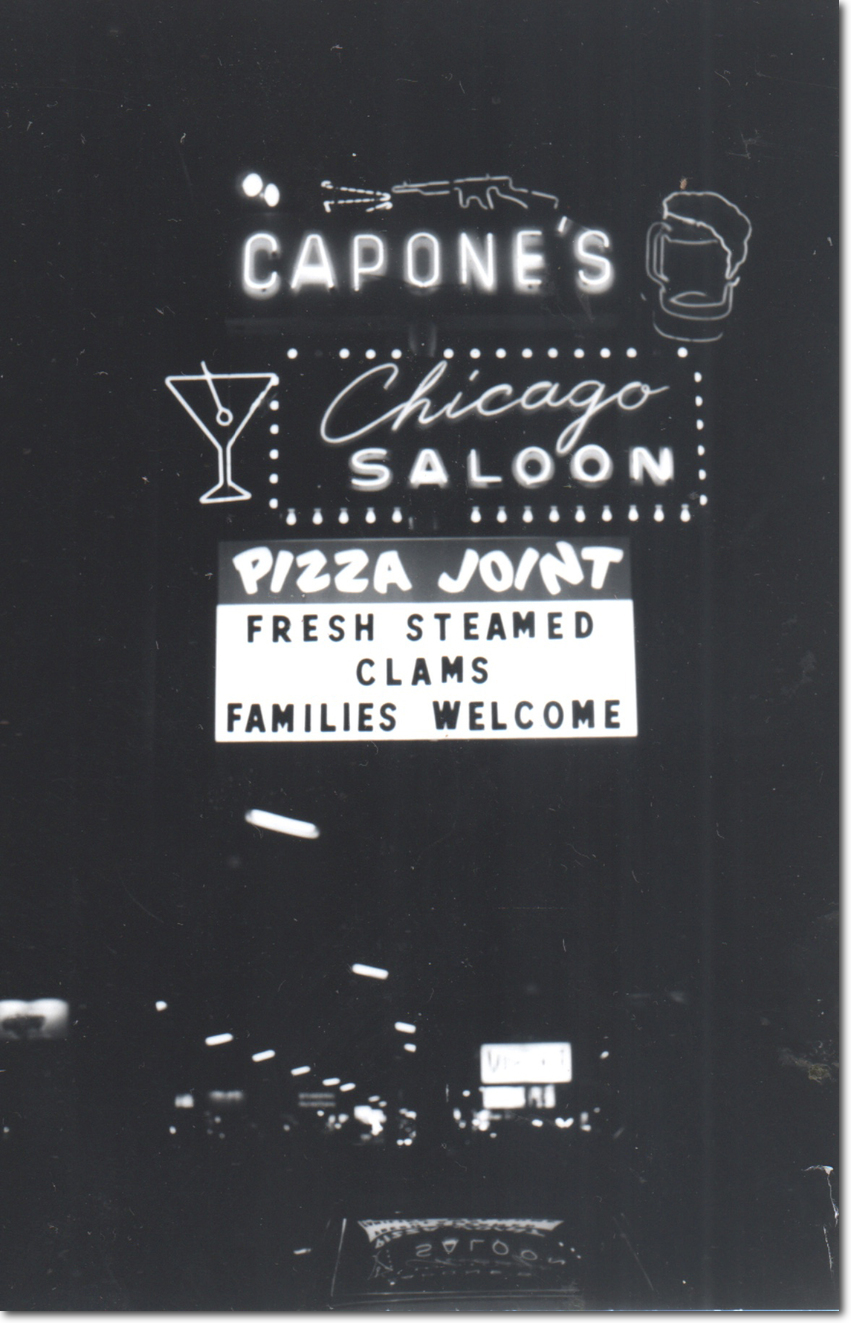 Night view of Capone's large neon sign advertising steamed clams and families welcome.
