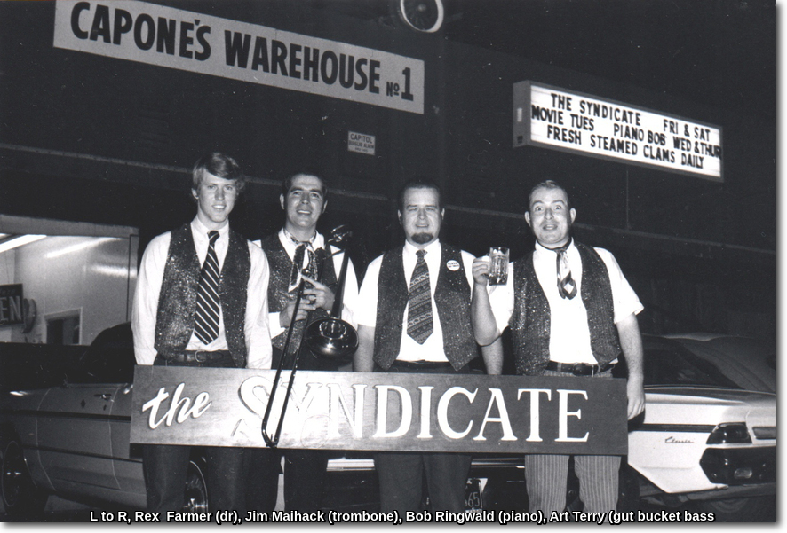 Photo of the Syndicate Musicians standing outside Capone's. Rex Farmer (dr), Jim Maihack (trombone), Bob Ringwald (piano), Art Terry (gut bucket bass)